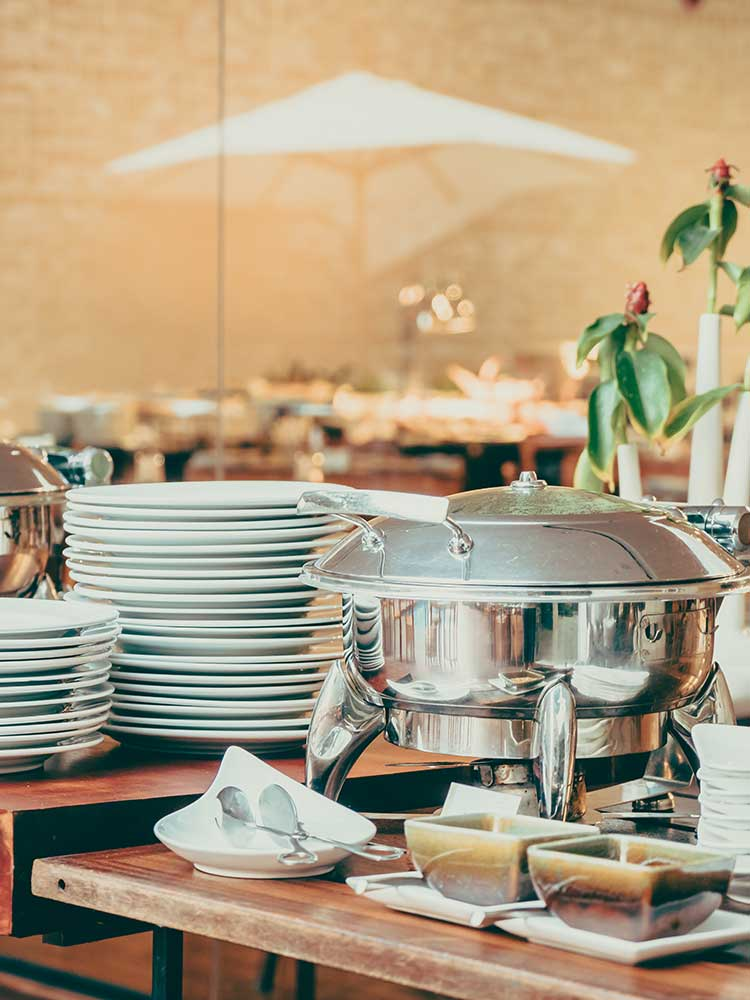 Arrangement of plates & chafing dishes in a Vegetarian catering set-up